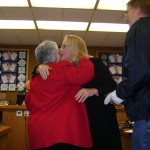 Councilwoman Rocha congratulates new Trustee Joy Motts as her brother Kerry Motts looks on.
