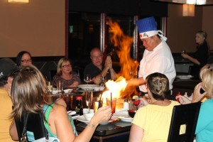 A chef entertains patrons while preparing their dinners at one of Kobe's 12 teppanyaki tables at their new restaurant in Antioch.