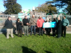 PG&E representative Tom Guarino (center in orange), with local officials and community leaders, presents a check to Take Back Antioch Founder Brittany Gougeon for $12,500 to rebuild the playground equipment at Antioch's City Park on Thursday, December 27, 2012.