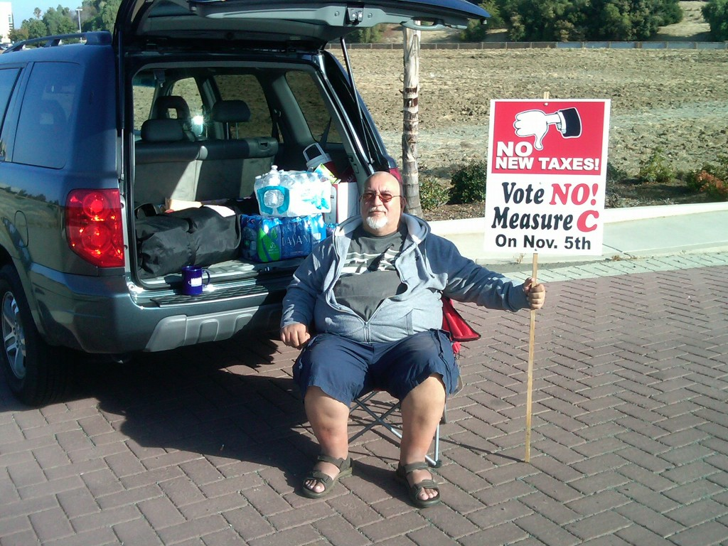 Antioch resident Karl Dietzel holds a No on Measure C campaign sign at the entrance of In-Shape on Lone Tree Way, on Friday morning, October 11.