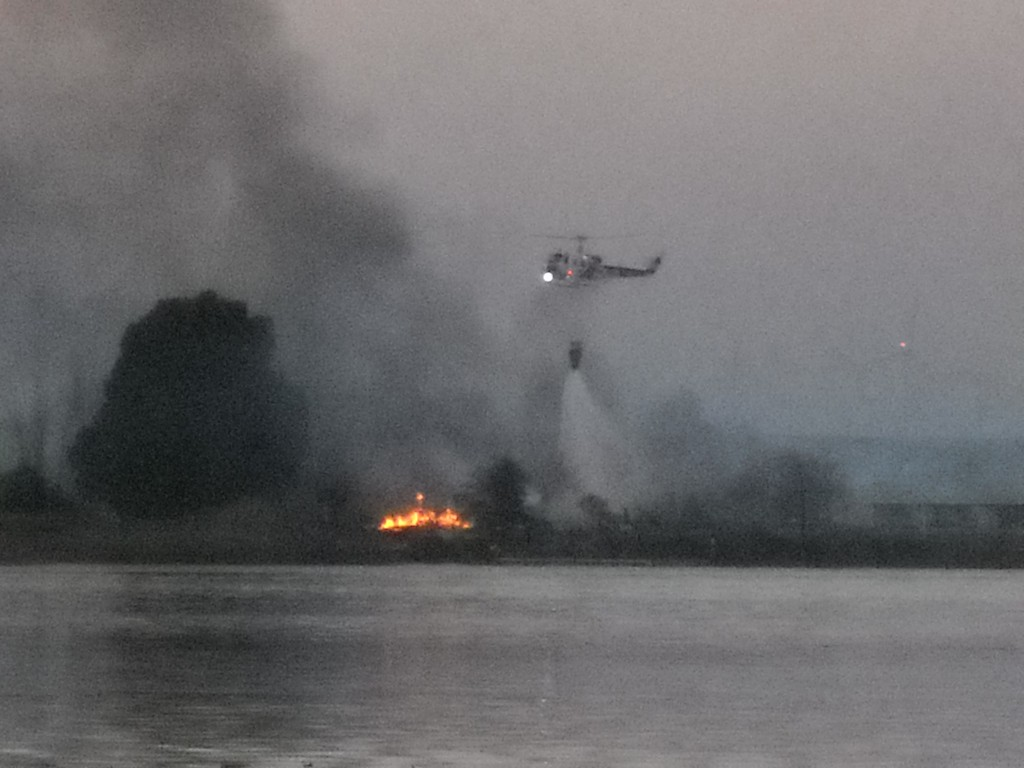 A helicopter attempts to douse the final flames on Kimball Island, during the fire, today. By Allen Payton