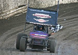 "(071115) Antioch Speedway Action -  Chris Magoon of Oakley, whose sprint car was sponsored by the late Jeremy ""Lumpy"" Sturgill, follows the memorial lap flying a checkered flag for the late Sturgill.  photo by mike Adaskaveg"