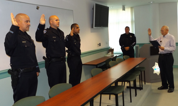 New Antioch Police Officers Corey Blumberg, Jacob Ewart and Rishi Negi are administered the oath of office by Antioch City Clerk Arne Simonsen as Chief Allan Cantando looks on, during a ceremony on Thursday, July 30, 2015.