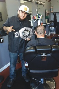Derek, in Ajja's, with his belt and a new design on a client's head.