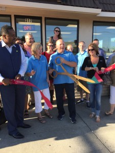 Owner Paul Spangenberg cuts the ribbon, while his wife Georgia, Mayor Wade Harper (left) on others watch.