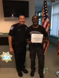 Chief Cantando presents Citizens Academy graduate Lorenzo Macon with his diploma and gifts.