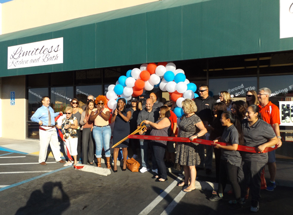 Business and community leaders cheer as owners Lou and Vanessa Hellmann, with scissors, cut the ribbon to officially open their new business Limitless Kitchen & Bath in Antioch, Thursday afternoon.