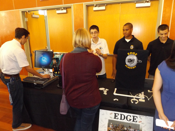 Antioch High School juniors Kevin Roldan, Darian Quinn and Robert Gochenouer speak with Amanda Hauf, a chemical engineer with Dow Chemical in Pittsburg, while junior Hudson Preece works the laptop at the EDGE Academy display.
