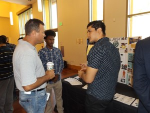 Deer Valley High students, junior Jafar Khalfani-Bey, center and senior Rahmat Omari, speak with Antioch business owner Ken Turnage at the Law & Justice Academy display.