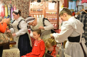 Proper young ladies have their hair beautifully braided at the Great Dickens Christmas Fair.