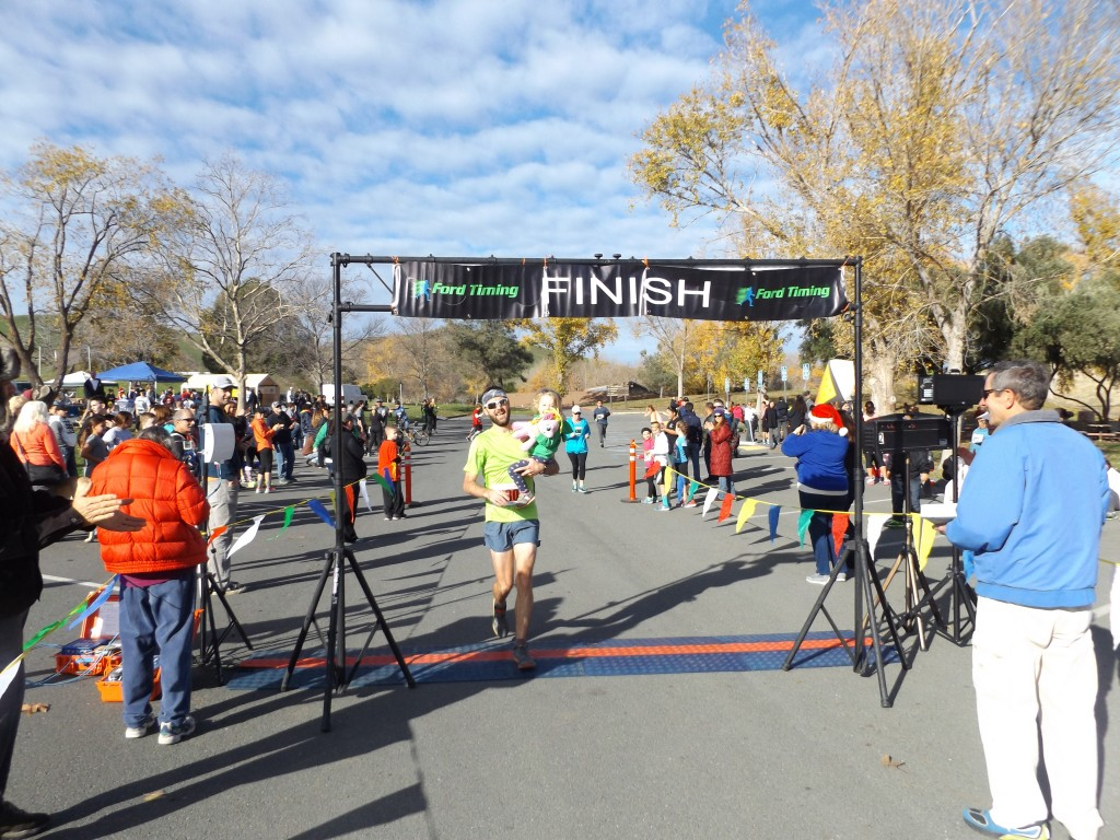 Overall 10K Run winner Brian Mohrlant crosses the finish line after picking up his daughter near the end of the race.