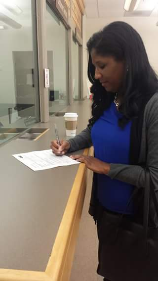 Wilson signs papers at the Contra Costa County Elections Division office. from her Facebook page.