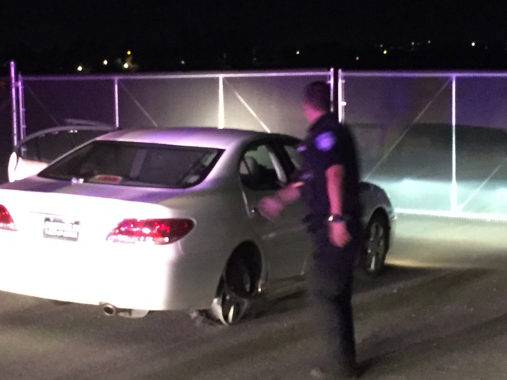 The suspect's car with the rear passenger tire worn down to the wheel.