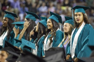 Deer Valley girl grads stand for their turn to receive their diplomas.