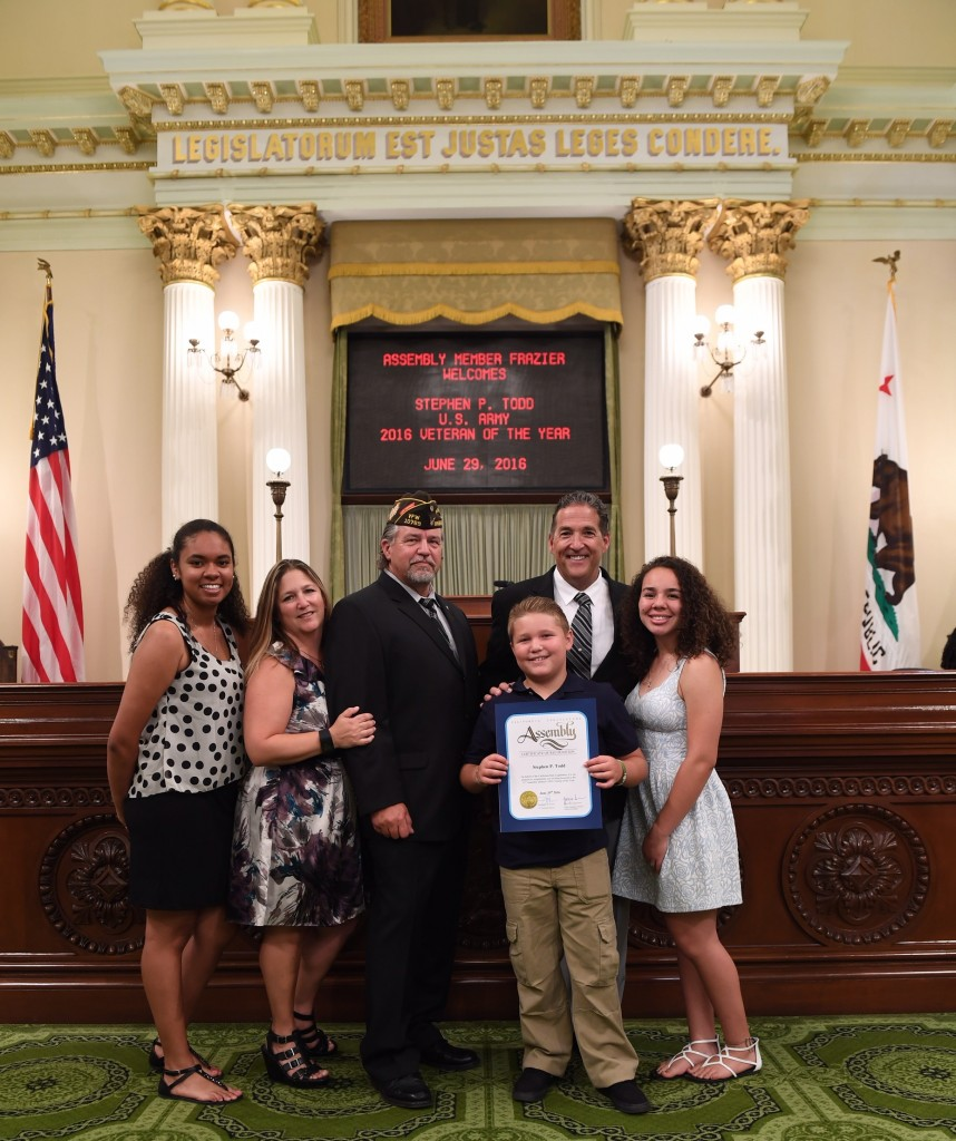 Stephen Todd and his family with Assemblyman Frazier on the floor of the State Assembly.