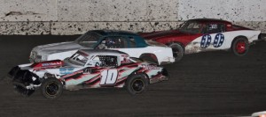 Guy Ahlwardt #10 moves by Danny Jones #66 on the last lap of the Hobby Stock race as Chris Sorensen #00 runs a very close third.  Photo By Paul Gould Photography