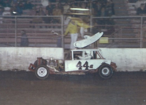 Jerry Hetrick #44a takes a checkered flag in his track record holding Sportsman in 1975.  Photo From The Jerry Hetrick Collection.