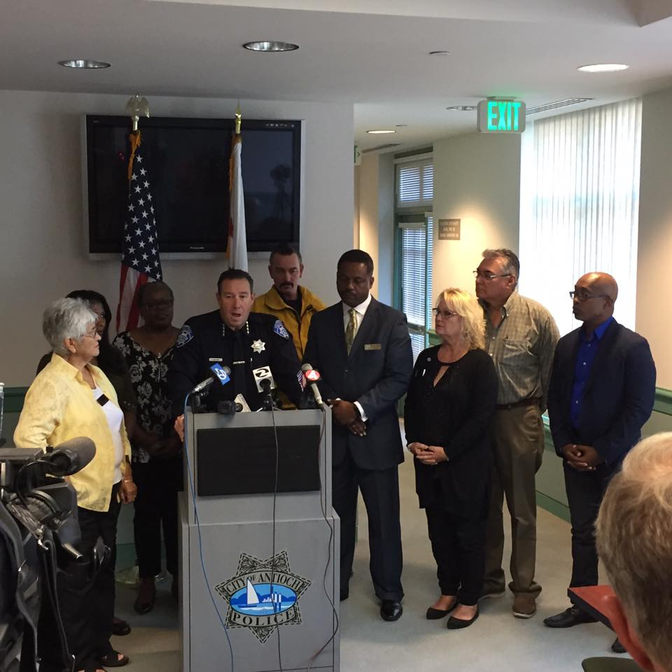 Antioch Police Chief Allan Cantando is joined by Antioch Mayor Wade Harper, (in suit, right), all four council members and others, as he announces the arrest of two suspects in last Wednesday's hate crime, at a press conference Tuesday afternoon.