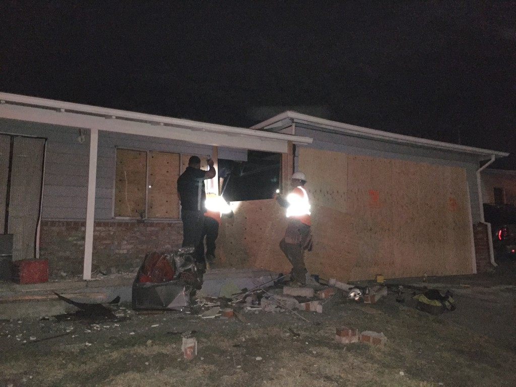A crew was still working at 11:00 p.m. to board up the house one Lone Tree Way in which a drunk truck driver crashed into Thursday evening. Photo by Allen Payton