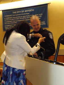 New Antioch Police Officer Garrett McKenzie is pinned with his badge by his wife.