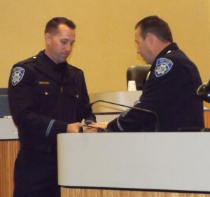 New Antioch Police Officer Jason Cash is presented with his badge by Chief Cantando.