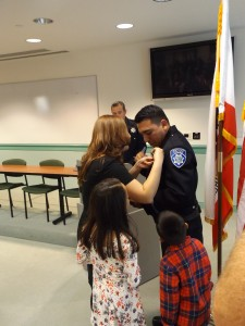 Officer Millan's wife pins on his new badge, as his daughter, son and Chief Cantando look on.