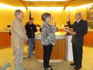 City Treasurer Donna Conley is sworn in for a fourth term by City Clerk Arne Simonsen as her family looks on.