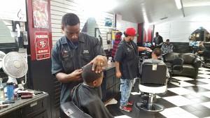 "Kalon ""K"" James cuts a style into a little boys hair."