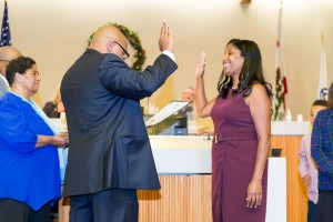 Re-elected Councilwoman Monica Wilson is given her oath of office by her brother Terrance, while their mother and Uncle