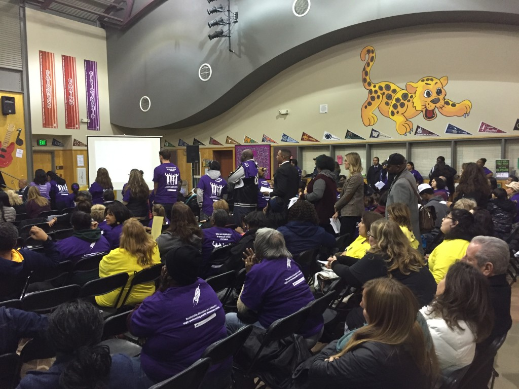 Supporters of the Rocketship charter school in Antioch line up to speak at Wednesday night's special school board meeting, as other supporters in purple shirts and opponents in yellow shirts listen.