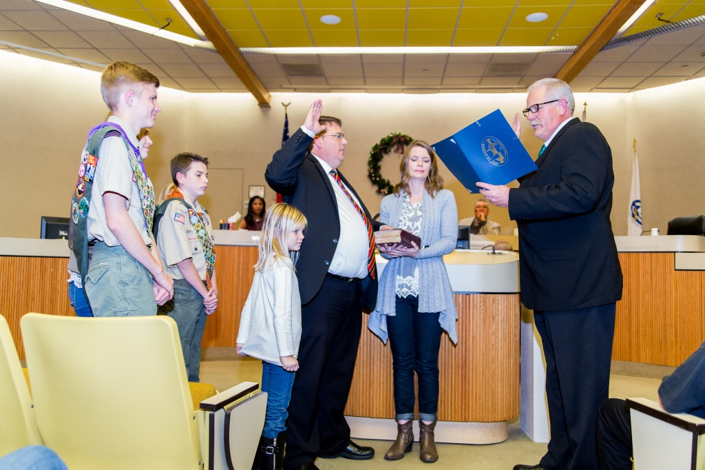 Dr. Sean Wright takes the oath of office administered by his uncle, Oakley Mayor Kevin Romick, with Wright's wife Lani holding the Bible, and their children by his side, during ceremonies, Thursday night. Photo by Michael Pohl.